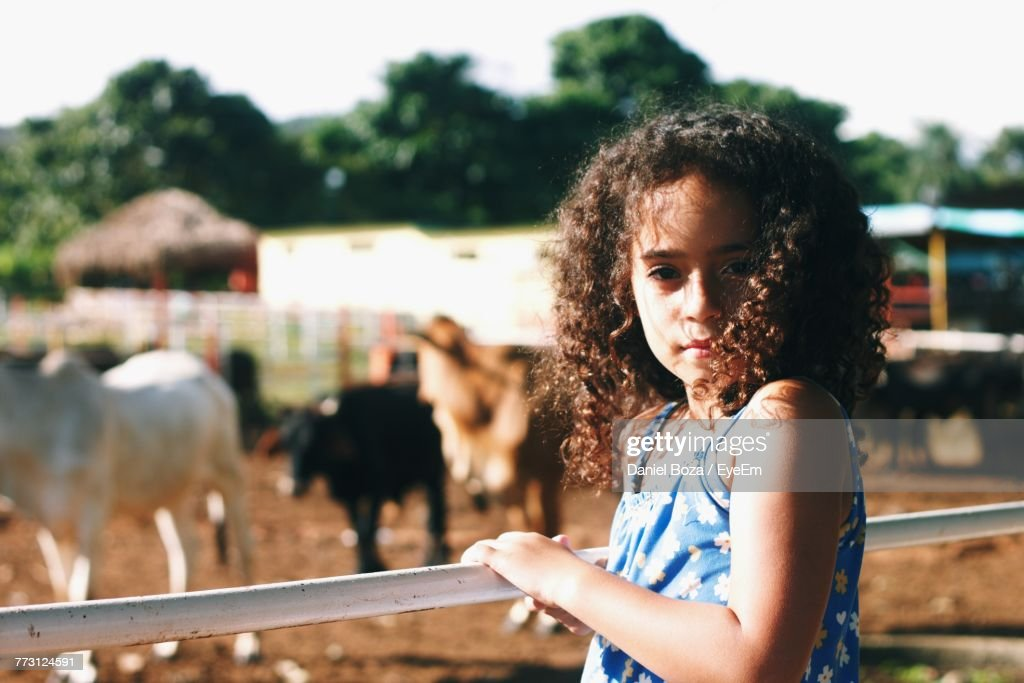 Portrait Of Girl Standing By Railing At Barn : Photo