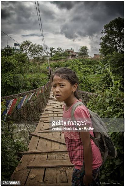 portrait of girl standing by rope bridge over river in forest against cloudy sky - népal photos et images de collection