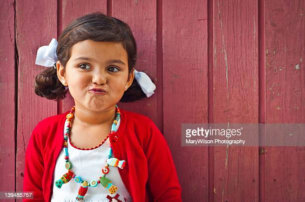 Portrait of girl standing in front of wooden wall