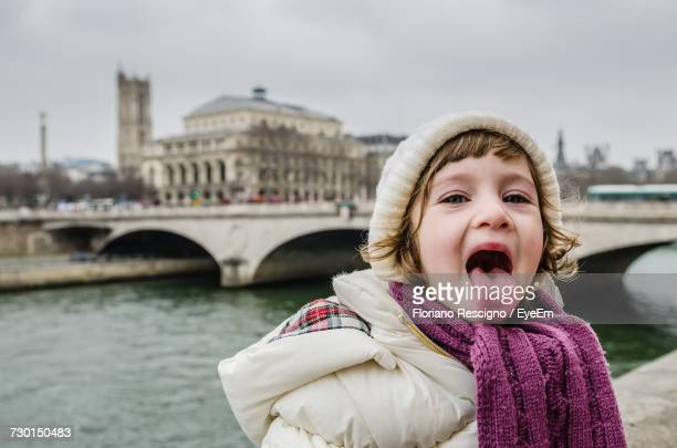 portrait of girl standing on bridge over river - little girl sticking out tongue stock photos and pictures
