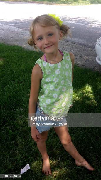 portrait of girl standing on grass at park - emery stock photos and pictures