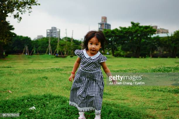 Portrait Of Girl Standing On Grassy Field