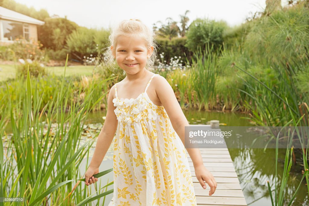 Portrait of girl (4-5) standing on jetty : Stock Photo