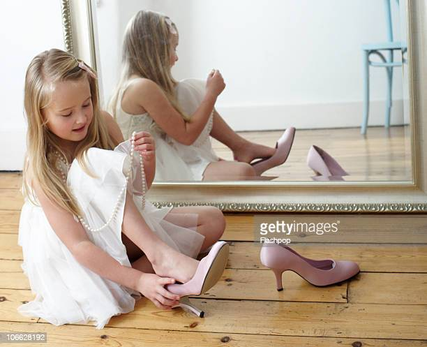 Portrait of girl trying on her mother's shoes