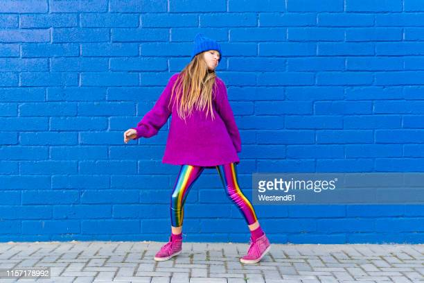 portrait of girl wearing blue cap and oversized pink pullover standing in front of blue wall dancing - multi colored hat stock pictures, royalty-free photos & images