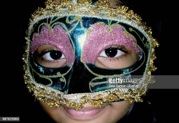 portrait of girl wearing carnival mask against black background - black mask disguise stock pictures, royalty-free photos & images