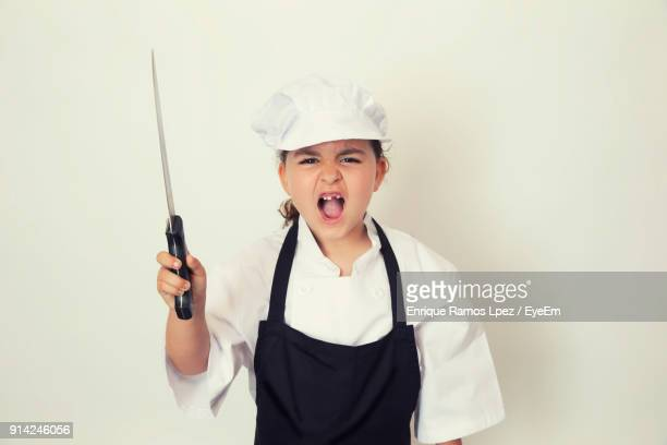 Portrait Of Girl Wearing Chef Costume Shouting Standing Against White Background