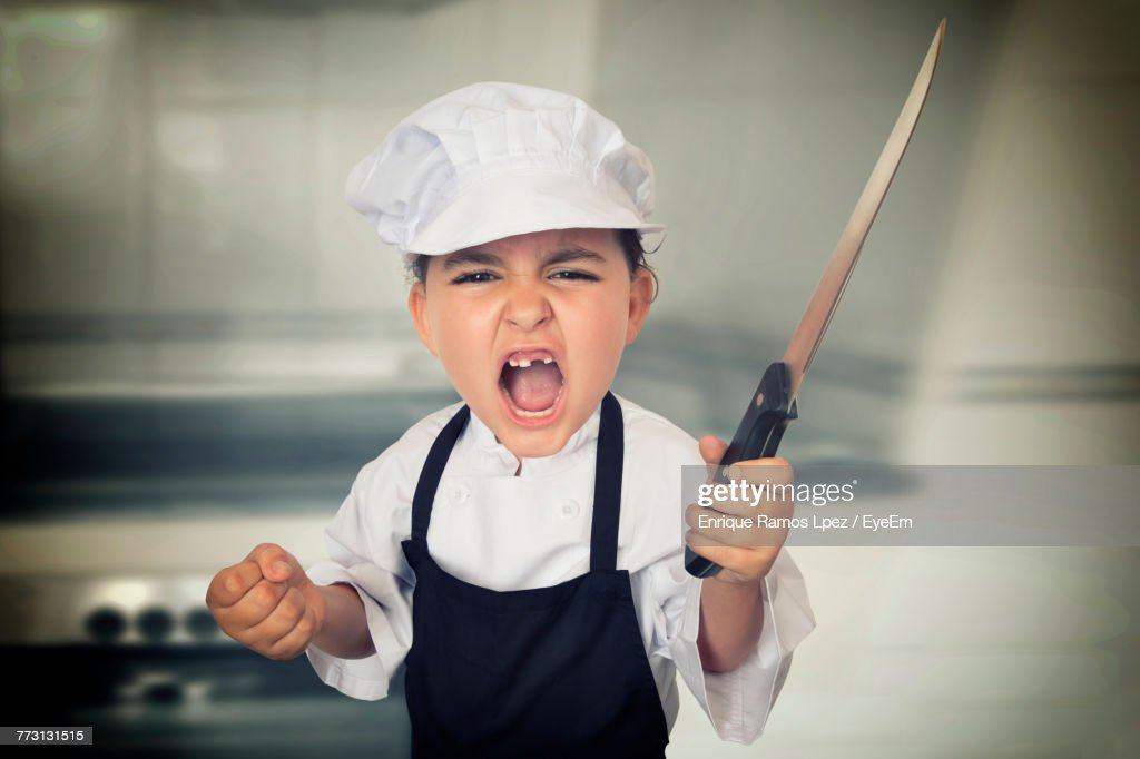 Portrait Of Girl Wearing Chef Uniform Holding Knife While Screaming In Kitchen : Photo