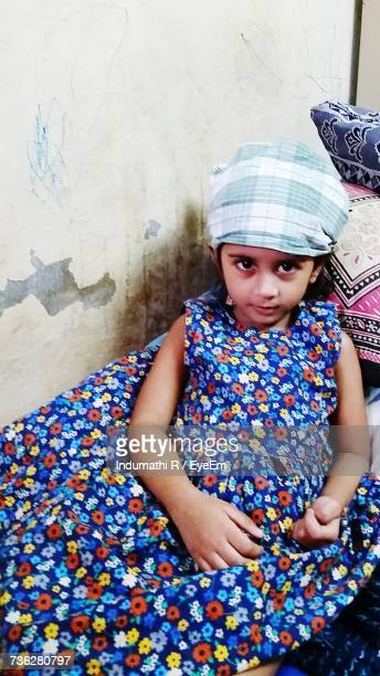 Portrait Of Girl Wearing Colorful Dress By Wall On Bed At Home