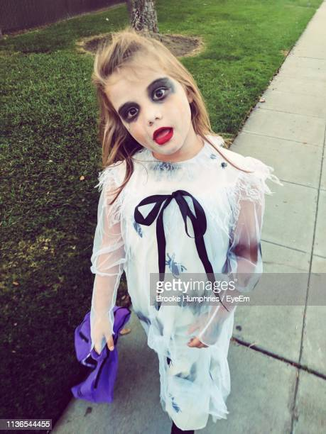 portrait of girl wearing costume and spooky make-up while standing on footpath - halloween zombie makeup stock photos and pictures