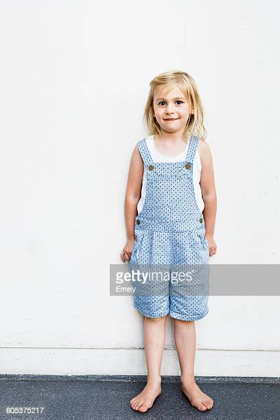 Portrait of girl wearing dungarees in front of white wall