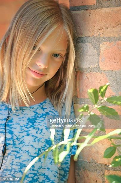 Portrait of girl wearing earphones leaning brick wall, Buonconvento, Tuscany, Italy
