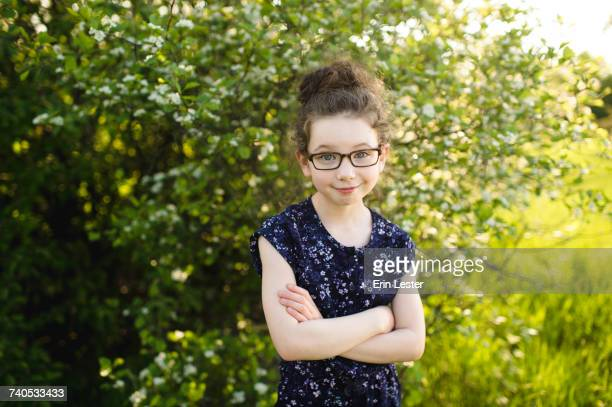 Portrait of girl wearing eye glasses in field with blossoming trees