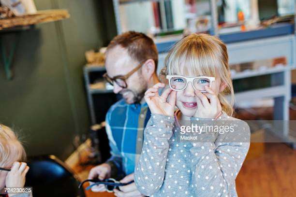 Portrait of girl wearing eyeglasses with family in workshop