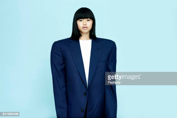 portrait of girl wearing huge business suit - adult imitation stock pictures, royalty-free photos & images