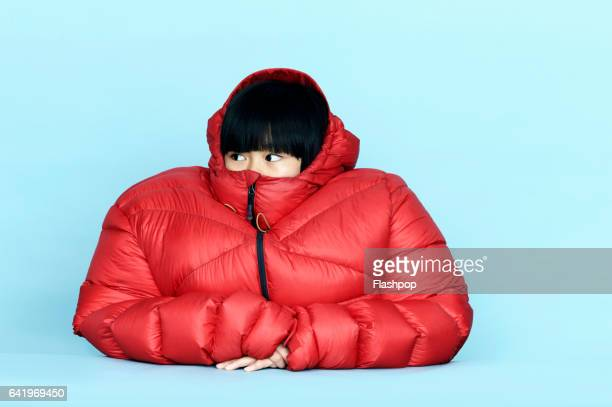 portrait of girl wearing huge coat - protection stock pictures, royalty-free photos & images