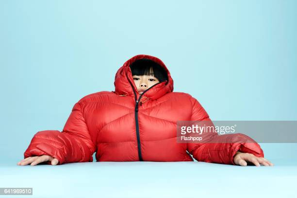 portrait of girl wearing huge coat - bizarre stock pictures, royalty-free photos & images