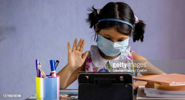 portrait of girl wearing mask on table at home - india stock pictures, royalty-free photos & images