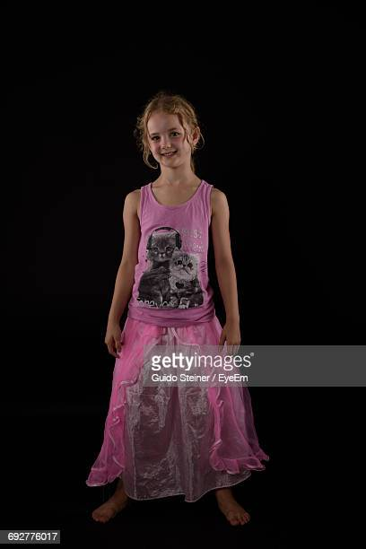 Portrait Of Girl Wearing Pink Frock While Standing On Black Background