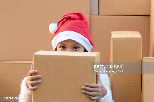 Portrait Of Girl Wearing Santa Hat While Holding Present On Face At Home