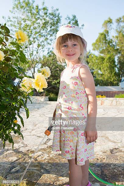 Portrait of girl wearing sunhat watering roses