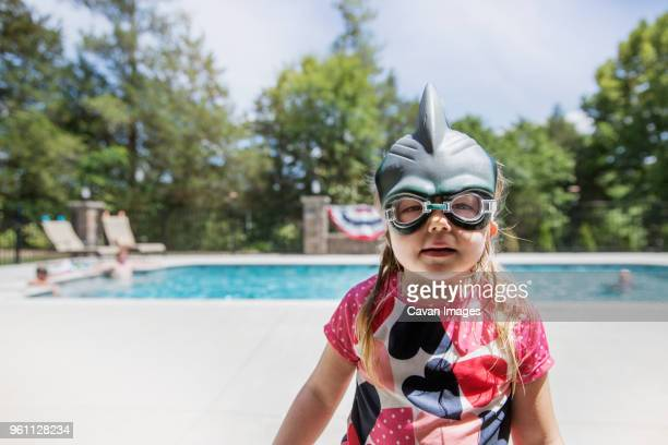portrait of girl wearing swimming goggles while standing against pool - one girl only stock pictures, royalty-free photos & images