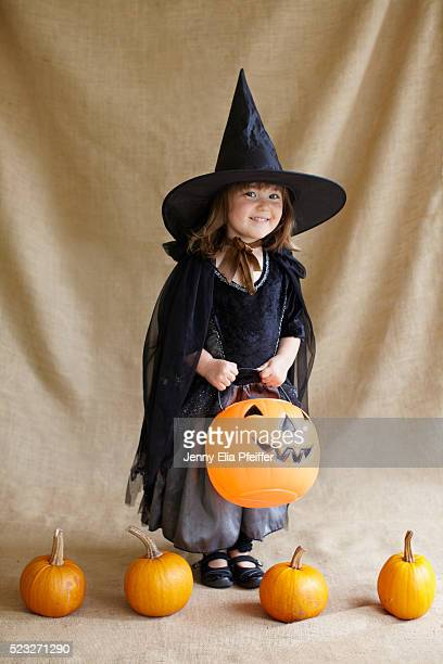 Portrait of girl (2-3) wearing witch costume holding pumpkin