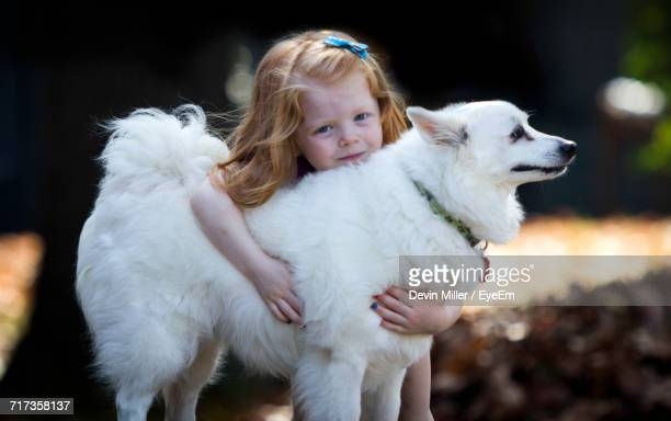 Portrait Of Girl With American Eskimo Dog In Park
