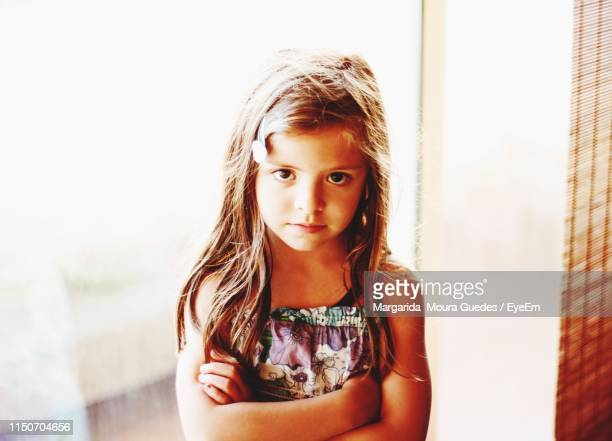 portrait of girl with arms crossed at home - moura stock photos and pictures