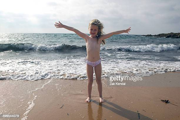 Portrait of girl with arms open on beach at Sardinia, Italy