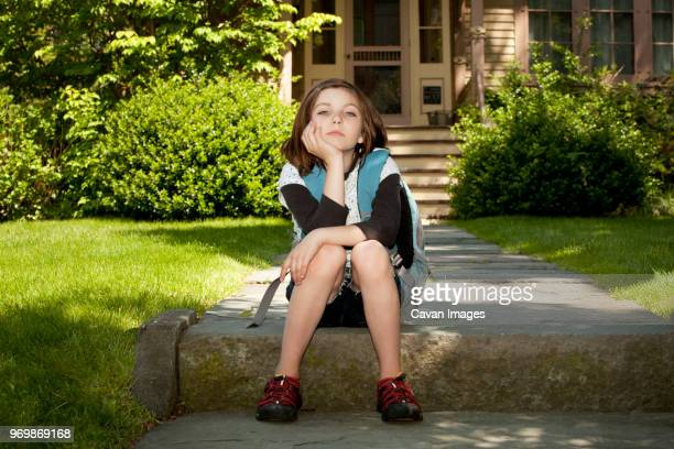 portrait of girl with backpack sitting on footpath - grey eyes stock pictures, royalty-free photos & images