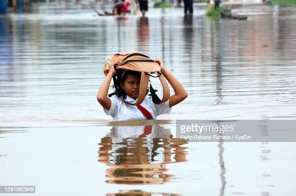 portrait of girl with bag on head walking in water - extreme weather stock pictures, royalty-free photos & images