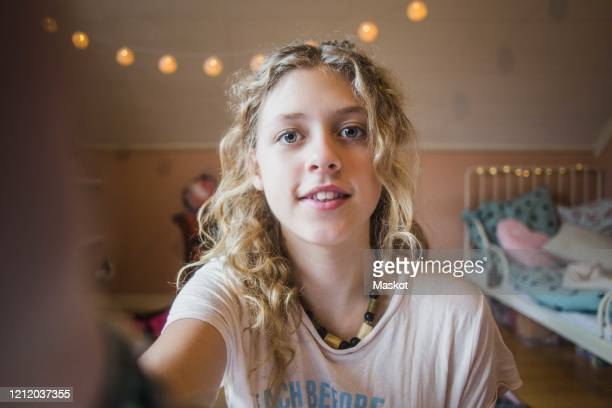 portrait of girl with blond hair taking selfie while sitting in bedroom - alleen één meisje stockfoto's en -beelden