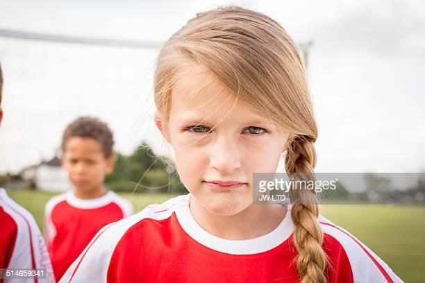 portrait of girl with blonde hair wearing football - fußballtrikot stock-fotos und bilder