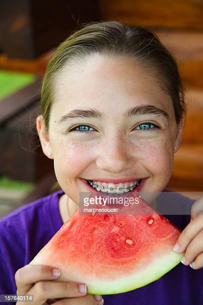 Portrait de femme avec des yeux bleus et des bretelles manger pastèque