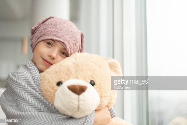 ritratto di ragazza con il cancro con in mano un orsacchiotto - cancer illness foto e immagini stock