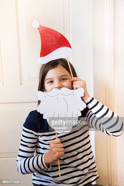Portrait of girl with Christmas cap and Father Christmas beard