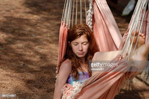Portrait of girl with closed eyes in a hammock