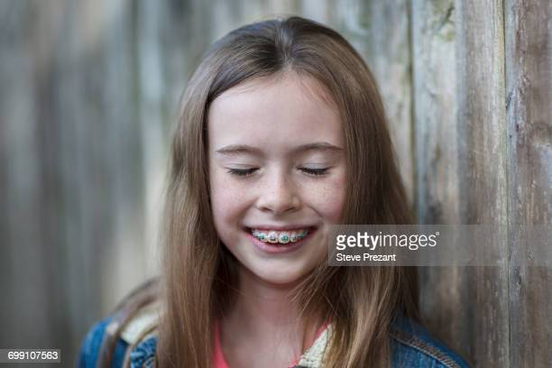 """portrait of girl with dental brace, eyes closed smiling"" - brace stock pictures, royalty-free photos & images"