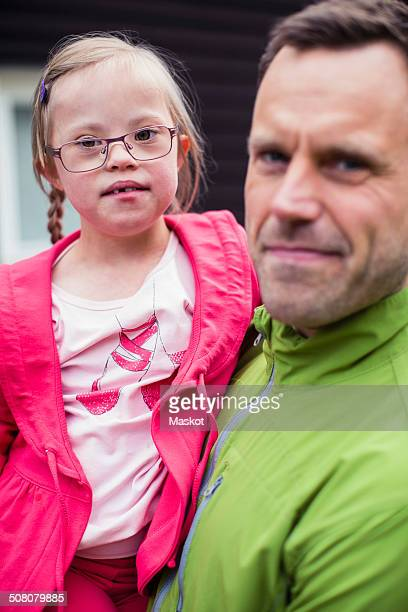 Portrait of girl with down syndrome carried by father