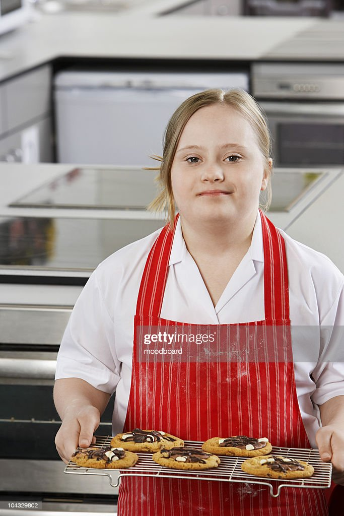 Portrait of girl (10-12) with Down syndrome carrying cookies on baking sheet : Stock Photo