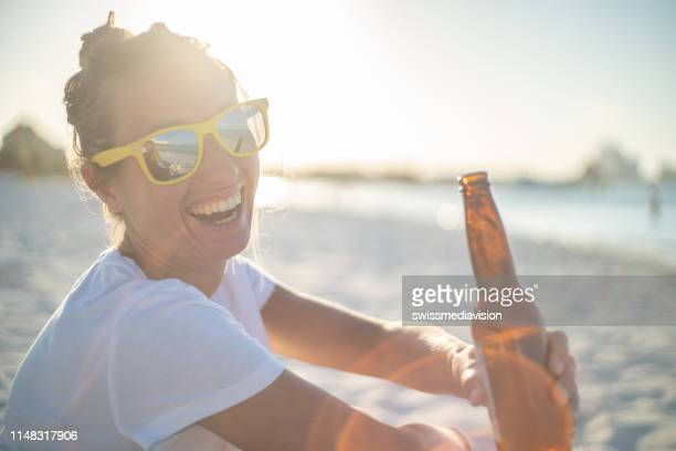 portrait of girl with drink in hand looking at boyfriend at sunset enjoying and celebrating vacations - mexican beer stock pictures, royalty-free photos & images