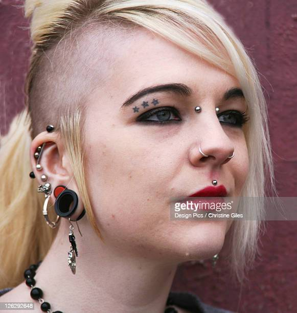 portrait of girl with full face piercings