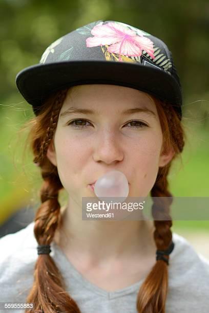 Portrait of girl with gum bubble wearing cap