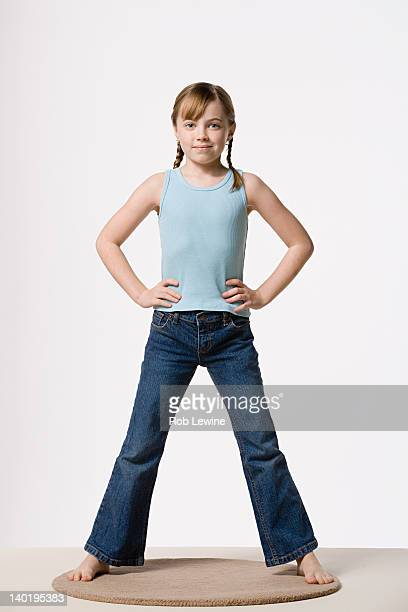 portrait of girl (8-9) with hands on hips, studio shot - hand on hip stock pictures, royalty-free photos & images