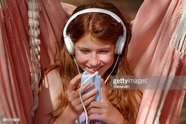 Portrait of girl with headphones and smartphone in a hammock