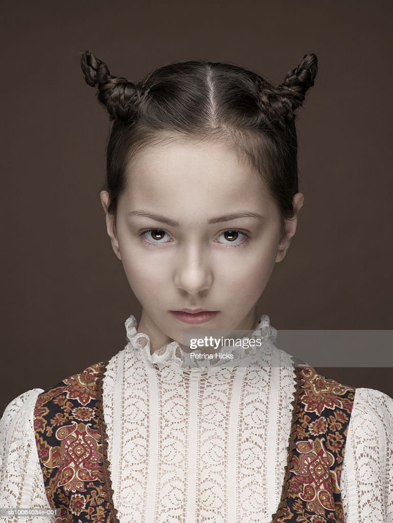 Portrait of girl (10-11) with hornlike pigtails, studio shot : Stock Photo