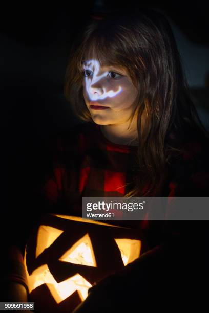 Portrait of girl with lighted Jack OLantern at Halloween