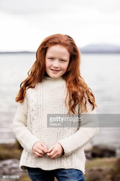 portret van een meisje met lange rode haren op de oever van het meer - 8 9 jaar stockfoto's en -beelden