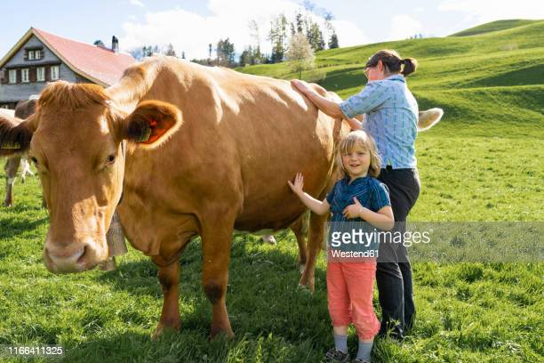 Portrait of girl with mother caring for cow on pasture
